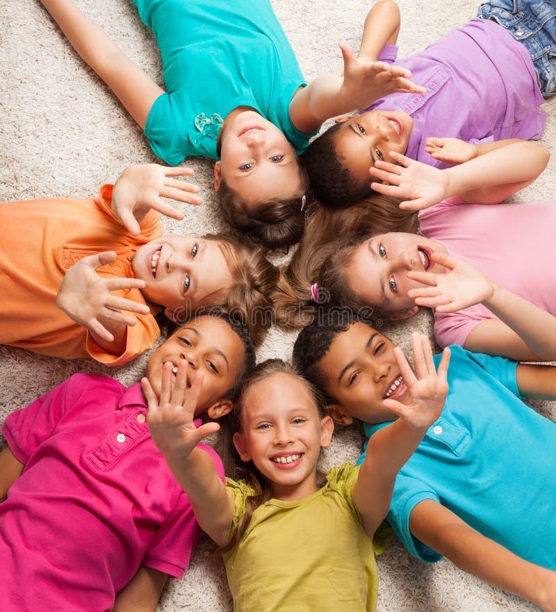 Les enfants en étoile forment la pose sur le florr photos libres de droits