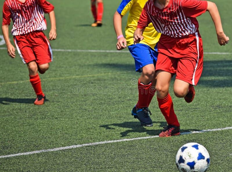 Les enfants en bas âge jouent le football images libres de droits