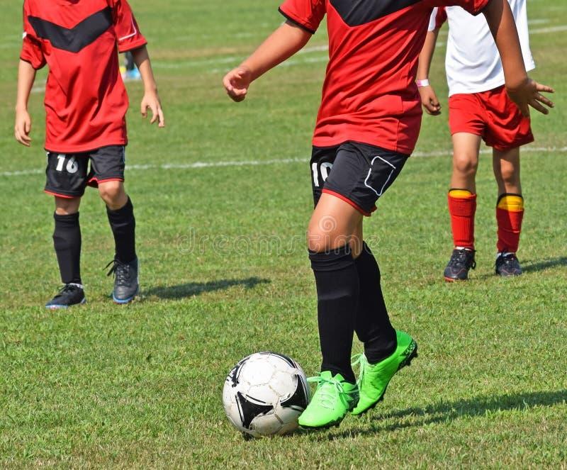 Les enfants en bas âge jouent le football photos stock