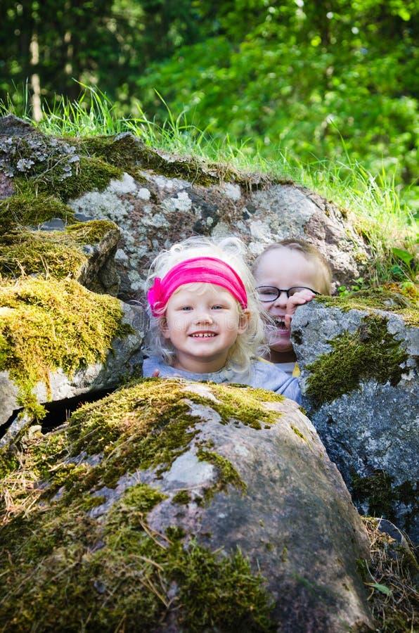 Les enfants en bas âge, le garçon avec la fille se sont cachés parmi les roches photos libres de droits
