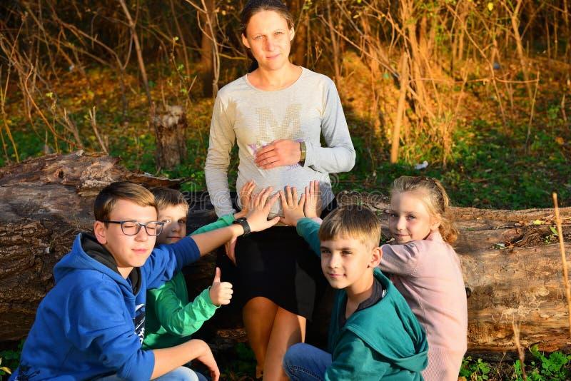 Les enfants en bas âge s'asseyent à côté d'une femme enceinte et tiennent leurs mains sur le ventre de leur mère dans la forêt en images stock