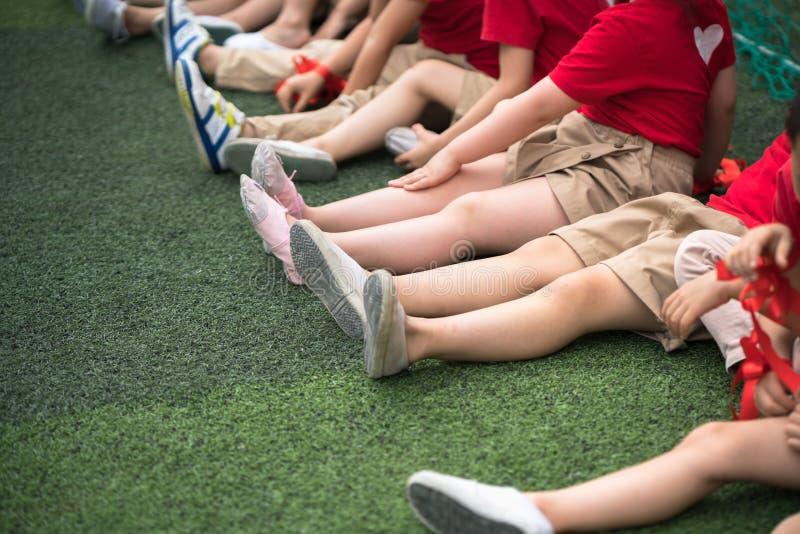 Les enfants en uniforme ont aligné des jambes se reposant sur l'herbe photo libre de droits