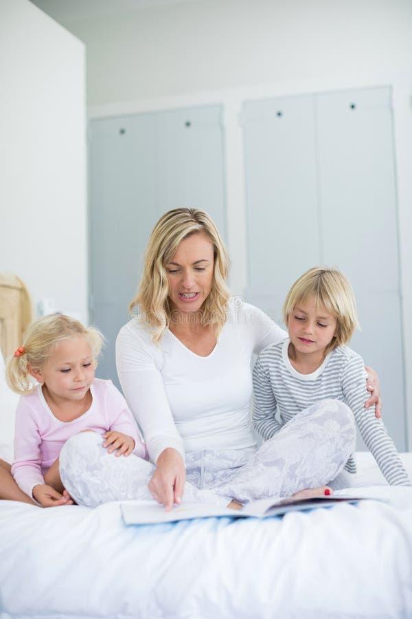 Les enfants et l'histoire de lecture de mère réservent dans la chambre à coucher photos libres de droits