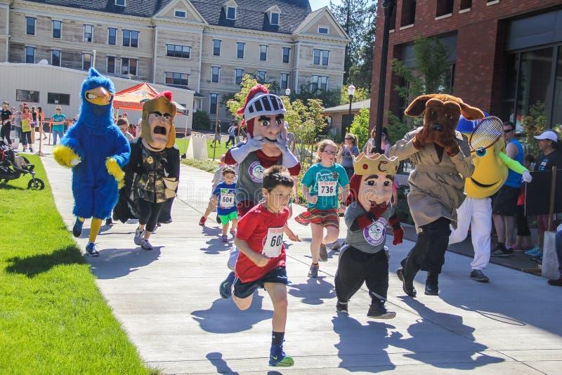 Les enfants et les mascottes d'équipe se précipitent dans la course de charité photographie stock libre de droits