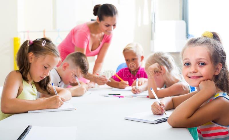Les enfants faisant l'écriture s'exerce avec l'aide du professeur dans la classe photographie stock