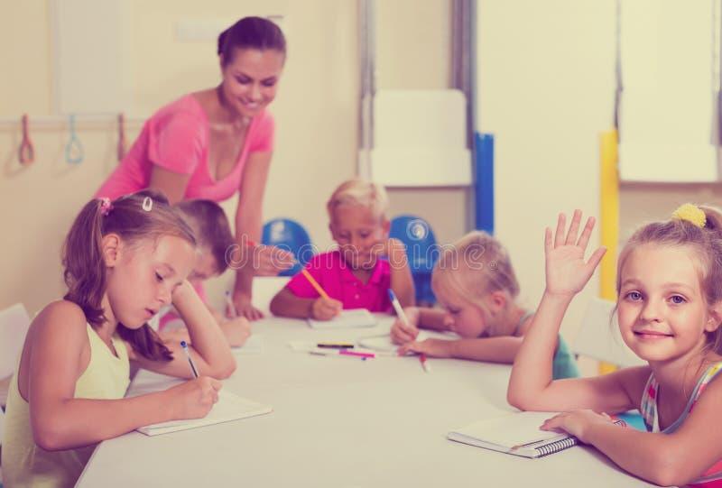 Les enfants faisant l'écriture s'exerce avec l'aide du professeur dans la classe image libre de droits