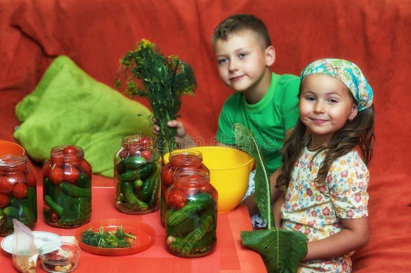 Les enfants font cuire des légumes pour l'hiver photo stock