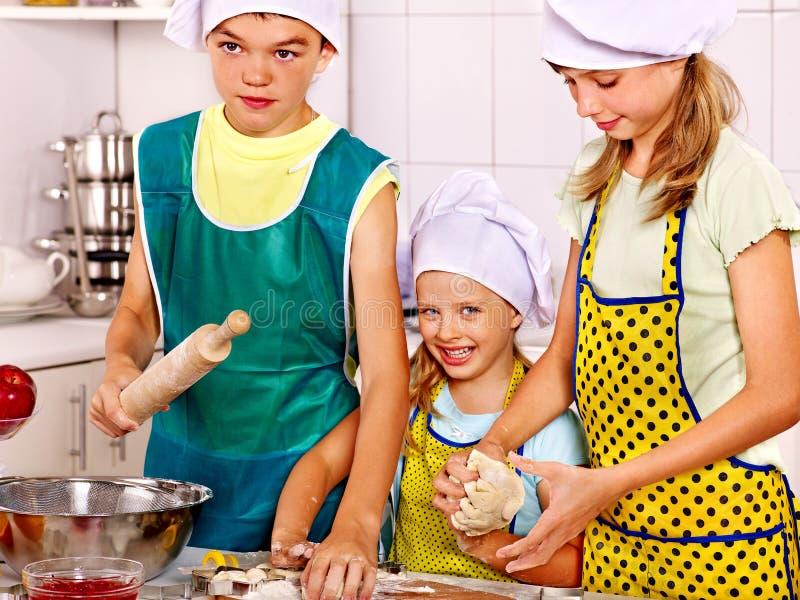 Les enfants font des biscuits cuire au four photos libres de droits