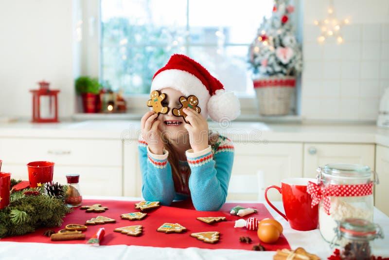 Les enfants font des biscuits cuire au four de Noël Cuisinier d'enfant pour Noël photographie stock libre de droits
