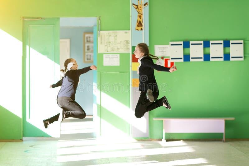 Les enfants gais sautent dans le couloir d'?cole photographie stock libre de droits
