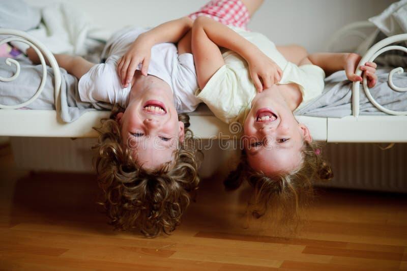 Les enfants, garçon et fille, vilains sur le lit dans la chambre à coucher images libres de droits