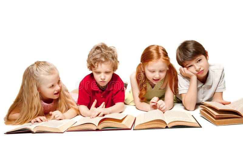 Les enfants garçon et filles s'étendant avec des livres d'isolement sur le blanc image stock