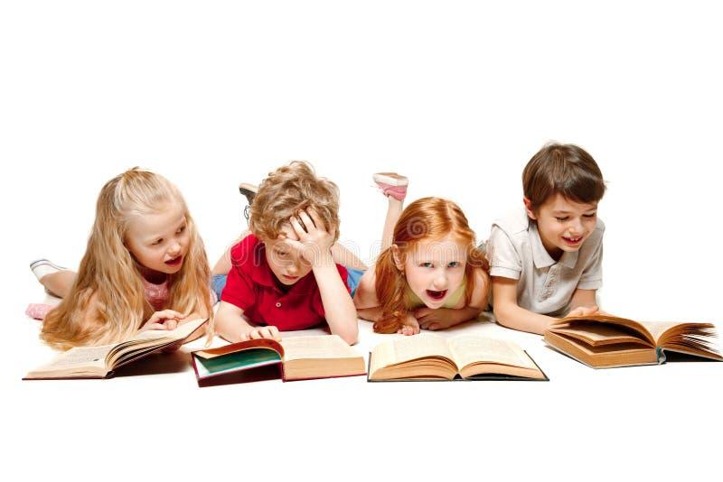 Les enfants garçon et filles s'étendant avec des livres d'isolement sur le blanc photographie stock libre de droits