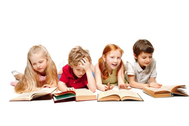 Les enfants garçon et filles s'étendant avec des livres d'isolement sur le blanc photographie stock