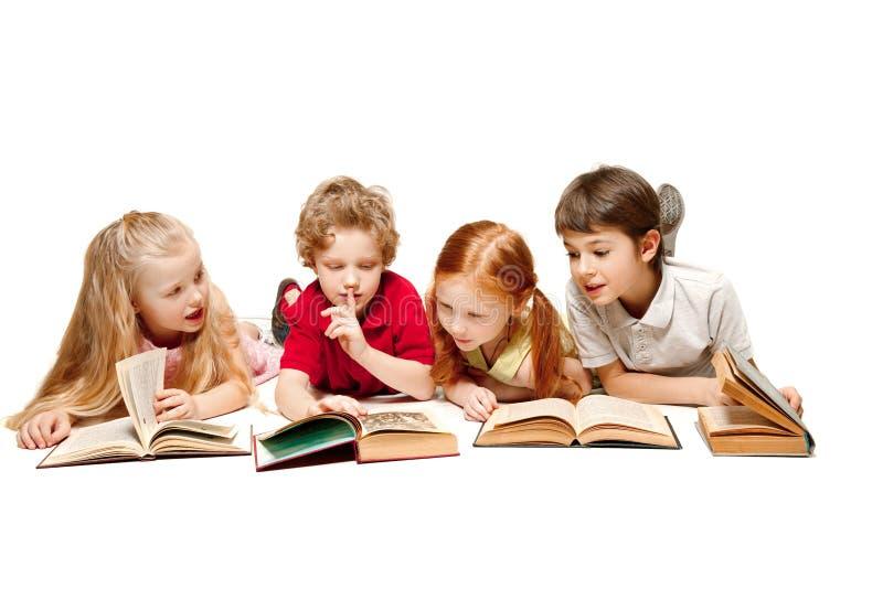 Les enfants garçon et filles s'étendant avec des livres d'isolement sur le blanc images libres de droits