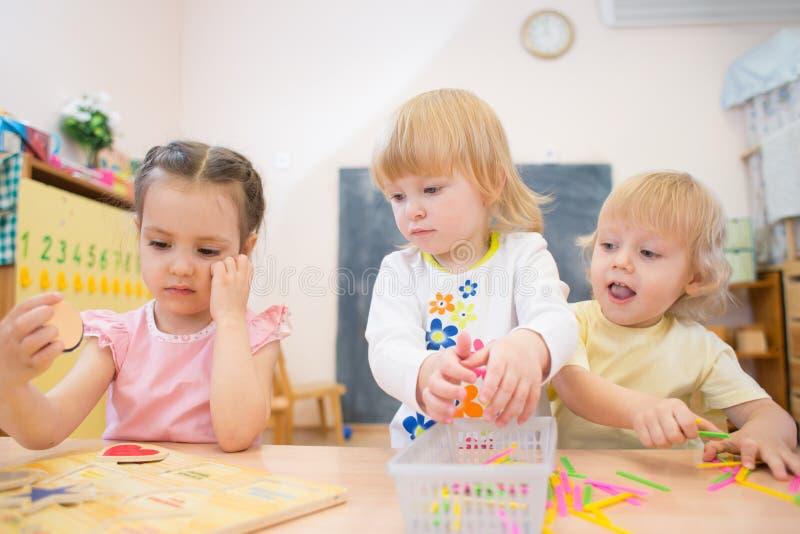 Les enfants groupent jouer le puzzle et d'autres jeux de société dans le jardin d'enfants photographie stock libre de droits