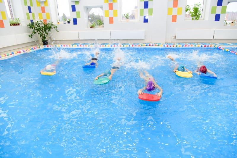 Les enfants groupent ? la piscine image stock