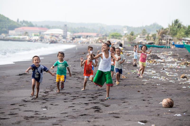 Les enfants groupent sur la plage avec le sable volcanique près du volcan Mayon, Philippines photographie stock libre de droits