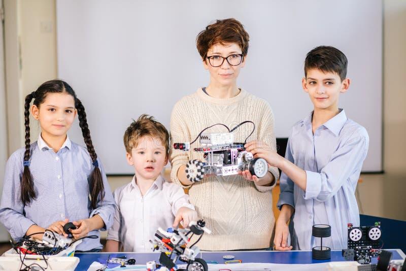 Les enfants heureux apprennent la programmation utilisant des ordinateurs portables sur les classes hors programme photos stock