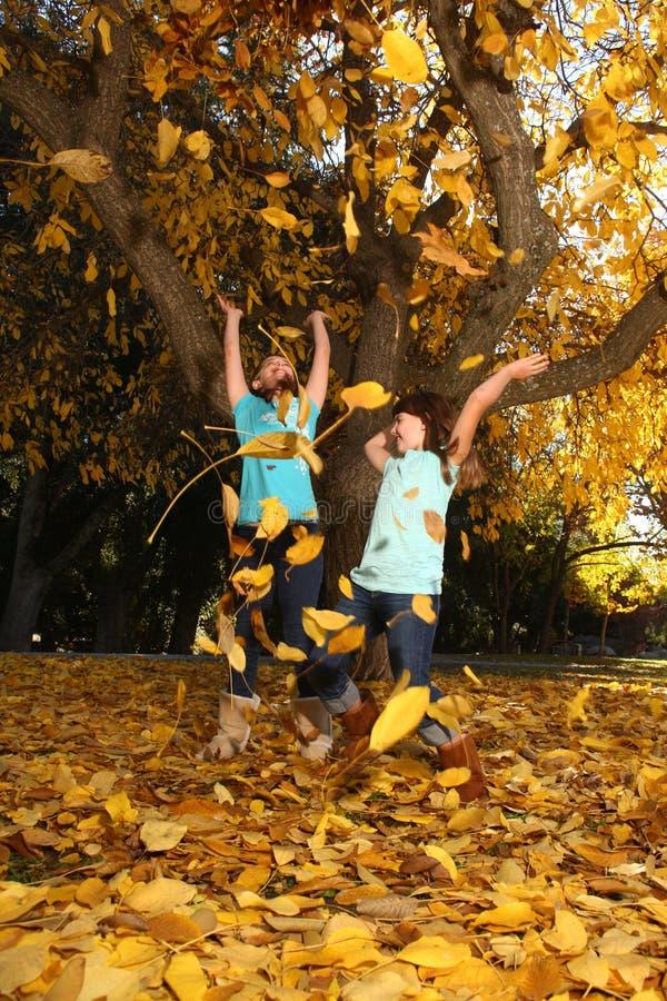 Les enfants heureux avec l'automne coloré part à l'extérieur photos libres de droits