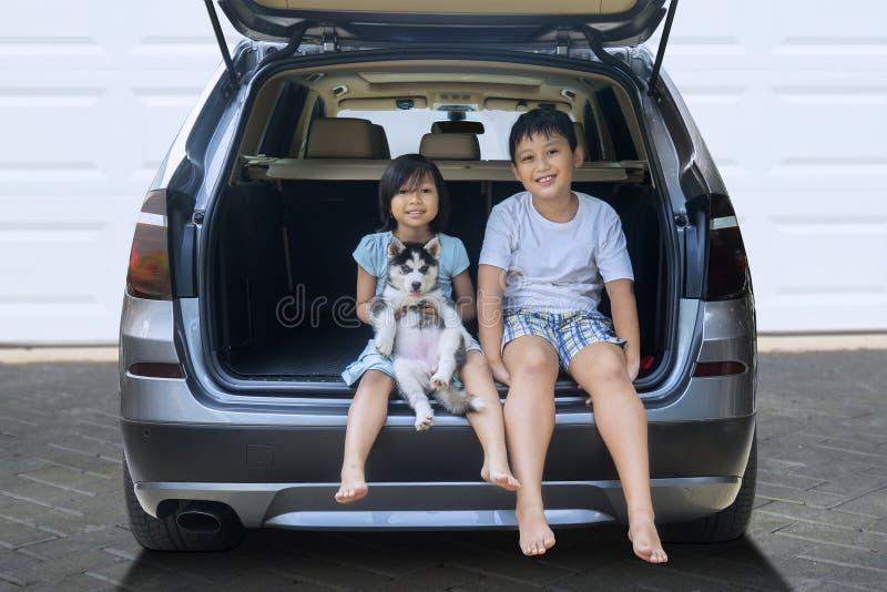 Les enfants heureux s'asseyent dans la voiture avec le chien enroué photo stock