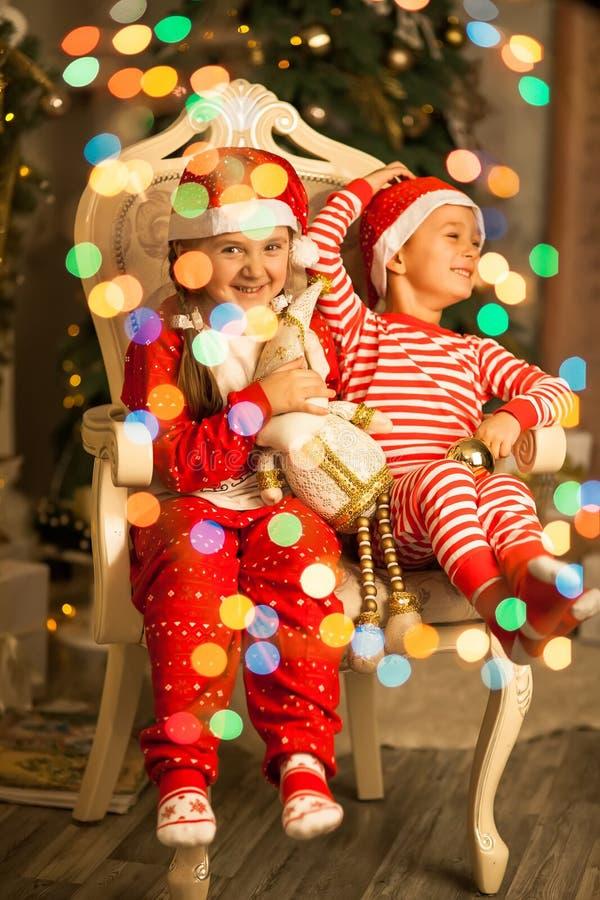 Les enfants heureux s'asseyent ensemble sur une chaise près de l'arbre de Noël photo stock