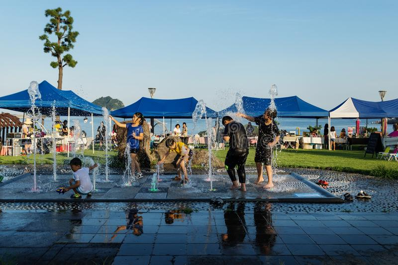 Les enfants jouant à une fontaine à la côte devant le souvernir se tient dans Seogwipo, île de Jeju, Corée du Sud photographie stock libre de droits