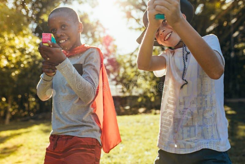 Les enfants jouant avec injectent des armes à feu dehors photographie stock