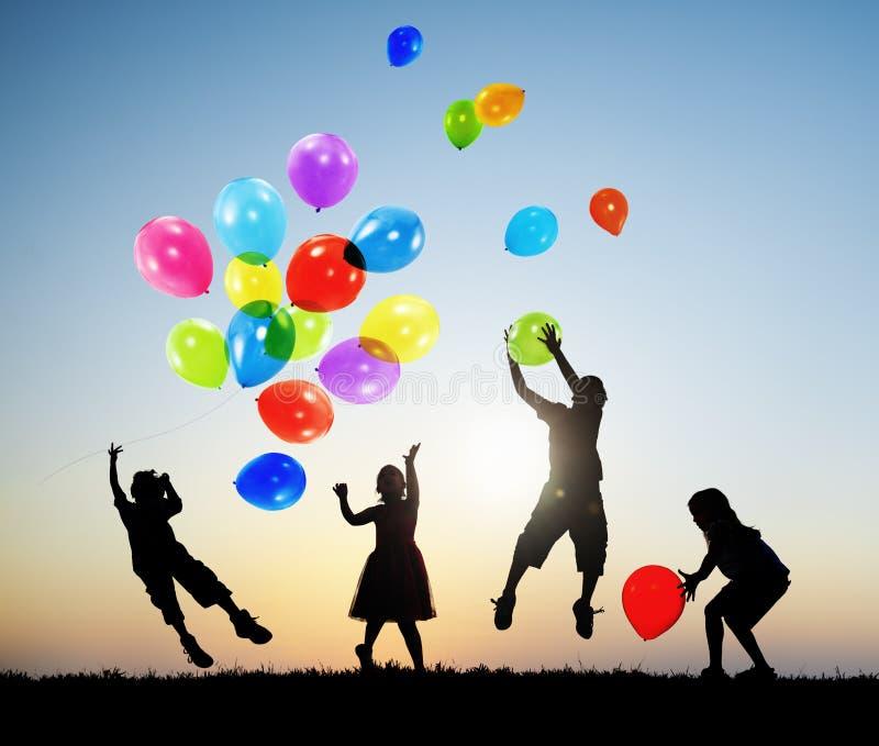 Les enfants jouant dehors monte en ballon ensemble images libres de droits