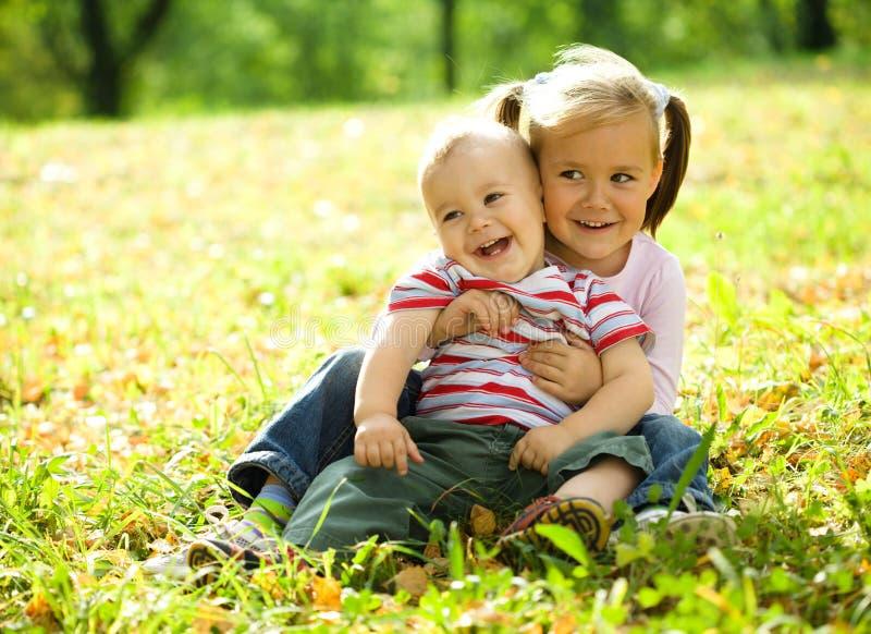 Les enfants jouent en stationnement d'automne photographie stock libre de droits