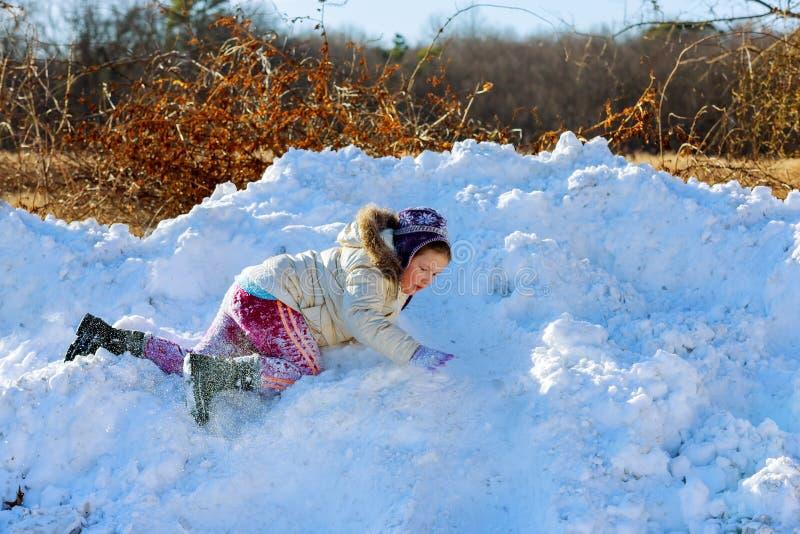 Les enfants jouent l'enfant heureux de saison extérieure d'hiver jouant dans la neige près d'une forêt photographie stock libre de droits