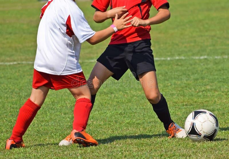 Les enfants jouent le football photos libres de droits