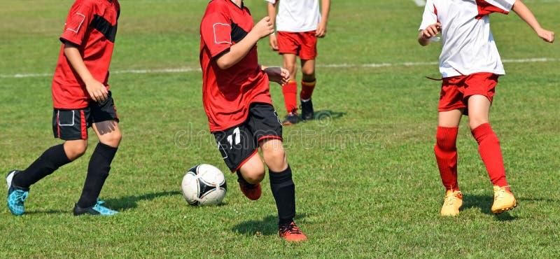 Les enfants jouent le football image libre de droits