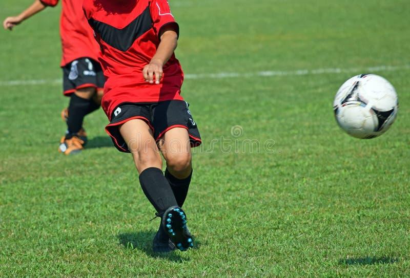 Les enfants jouent le football images stock