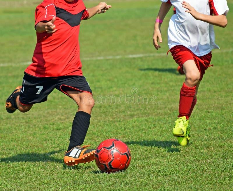 Les enfants jouent le football images libres de droits