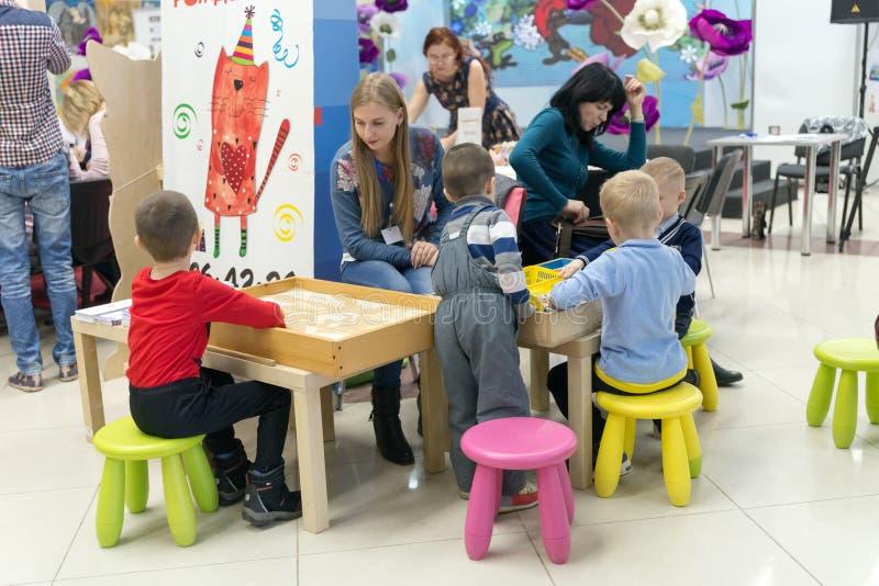 Les enfants jouent sous la surveillance adulte dans la salle d'enfants à la foire traditionnelle populaire des arts populaires fa photo stock