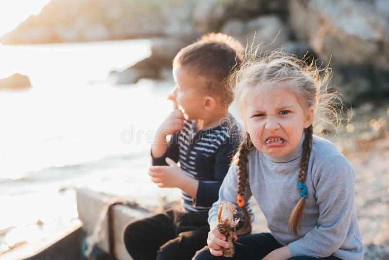 Les enfants, la fille et le garçon mangent de la viande de poulet sur la mer, la fille est fâchée et ne veut pas à image stock