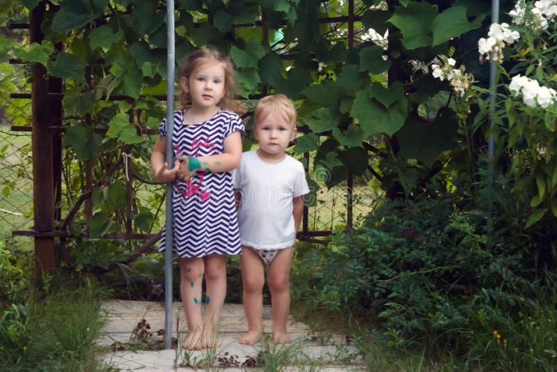 Les enfants, le frère et la soeur aux pieds nus se tiennent et regardent images libres de droits