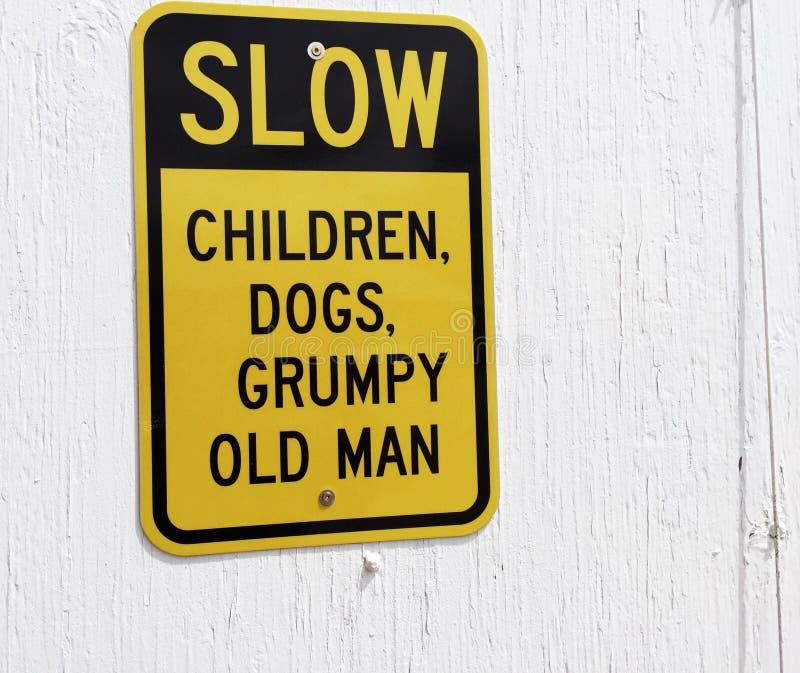 Les enfants lents, les chiens et le vieil homme grincheux signent images stock