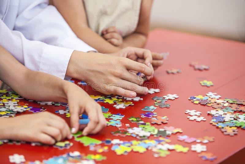 Les enfants, mains d'amis assemblent le puzzle sur la couleur de table photographie stock
