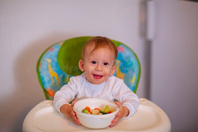 Les enfants mangent des légumes Enfant heureux mangeant les légumes sains photos stock