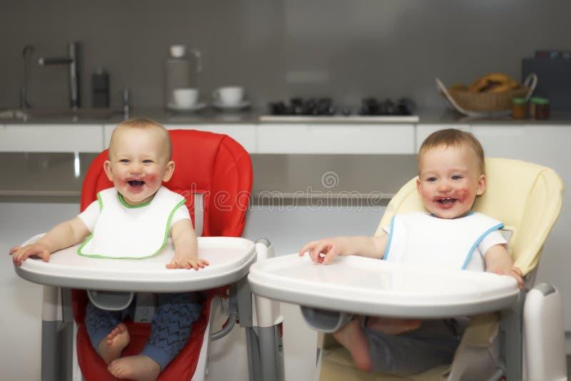 Les enfants mangent des myrtilles dans une haute chaise de bébé Les garçons ont un visage sale photos stock