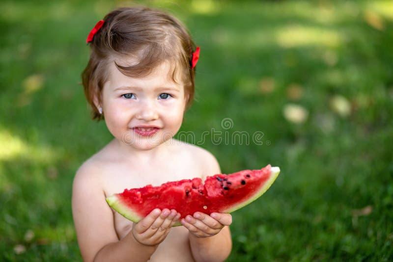 Les enfants mangent du fruit dehors Casse-croûte sain pour des enfants Petite fille jouant dans le jardin tenant une tranche de p image libre de droits