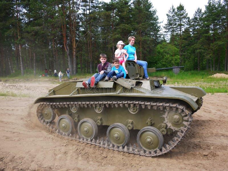 Les enfants montent sur le réservoir Le réservoir de la deuxième guerre mondiale roule des enfants et des adultes image libre de droits