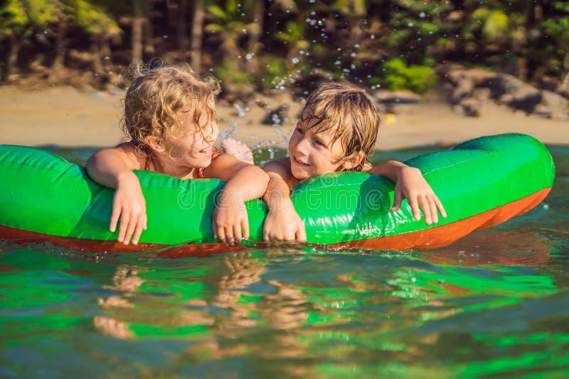 Les enfants nagent en mer sur un matelas gonflable et avoir l'amusement images stock