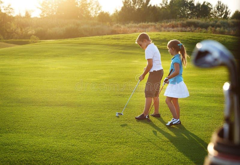 Les enfants occasionnels à un golf mettent en place tenir des clubs de golf image stock