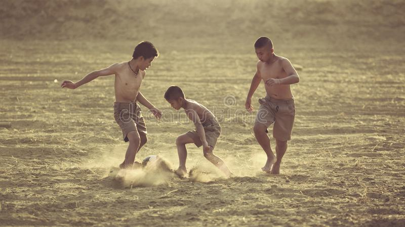 Les enfants ont l'amusement jouant le football dans le domaine image libre de droits