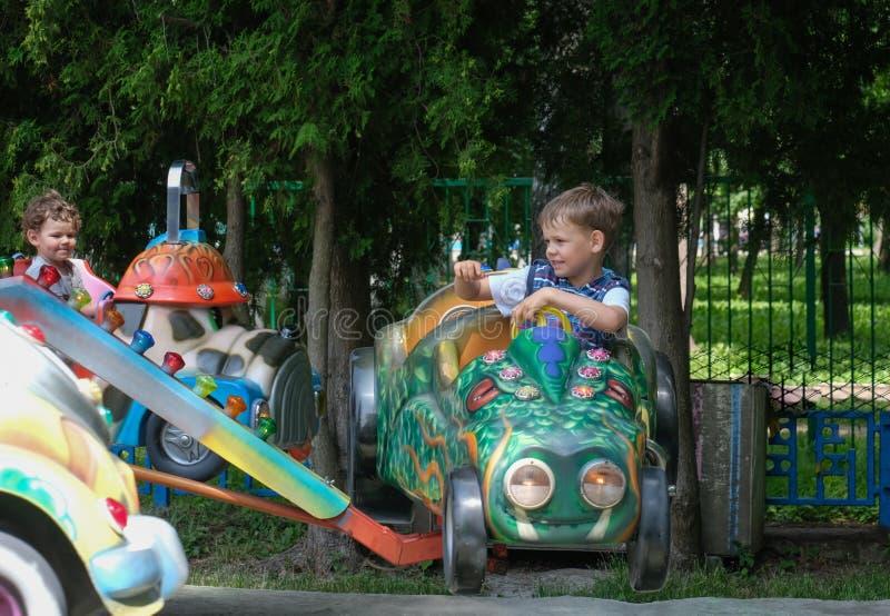 Les enfants ont l'amusement sur les tours avec des voitures dans le parc image libre de droits