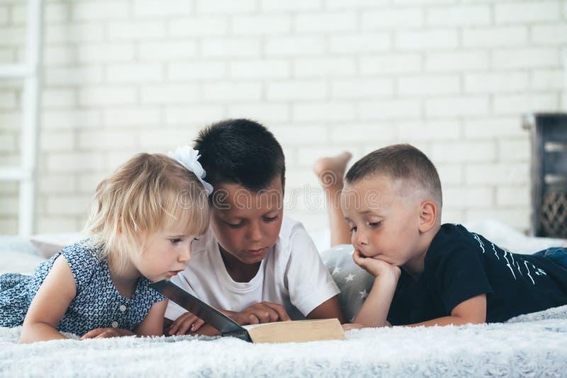 Les enfants ont lu une bible sur le lit images stock