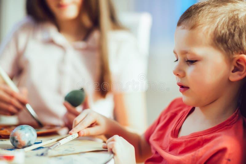 Les enfants ont peint des oeufs de pâques à la table images stock